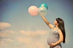Schwangere Frau auf einer Wiese mit blauem Himmel lizenzfreies stockbild