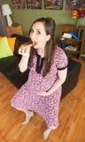 Schwangere Frau auf Sofa Eating Stockbilder