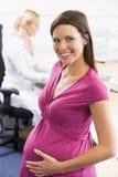 Schwangere Frau bei der Arbeit unter Verwendung des Telefonlächelns Stockbild