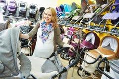Schwangere Frau chosing Pram Lizenzfreie Stockfotografie