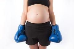 Schwangere Frau in den Boxhandschuhen Stockfoto