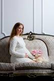 Schwangere Frau der Junge, die auf dem Sofa sitzt Lizenzfreie Stockfotos