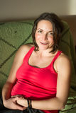 Schwangere Frau der Junge, die auf der Couch aufwirft lizenzfreies stockbild