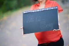 Schwangere Frau der Junge, die ein Zeichen hält Lizenzfreie Stockbilder