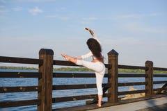 Schwangere Frau der Junge, die Yoga durch den Fluss tut Stockbilder