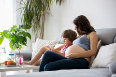 Schwangere Frau der Junge, ein Buch zu ihrem Jungen zu Hause lesend Lizenzfreies Stockfoto