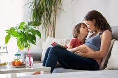 Schwangere Frau der Junge, ein Buch zu ihrem Jungen zu Hause lesend Stockfotos