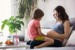 Schwangere Frau der Junge, ein Buch zu ihrem Jungen zu Hause lesend Lizenzfreie Stockfotografie