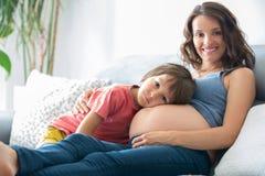 Schwangere Frau der Junge, ein Buch zu ihrem Jungen zu Hause lesend Stockbilder
