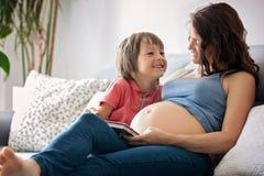 Schwangere Frau der Junge, ein Buch zu ihrem Jungen zu Hause lesend Stockfoto