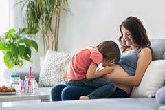 Schwangere Frau der Junge, ein Buch zu ihrem Jungen zu Hause lesend Lizenzfreie Stockbilder