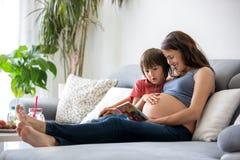 Schwangere Frau der Junge, ein Buch zu ihrem Jungen zu Hause lesend Stockfotografie