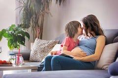 Schwangere Frau der Junge, ein Buch zu ihrem Jungen zu Hause lesend Lizenzfreie Stockfotos