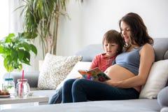 Schwangere Frau der Junge, ein Buch zu ihrem Jungen zu Hause lesend Lizenzfreies Stockbild