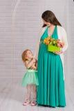 Schwangere Frau der Junge in einem Türkiskleid Lizenzfreie Stockfotos