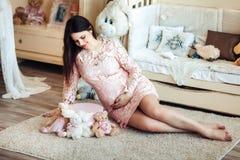Schwangere Frau der Junge in einem zarten rosa Kleid auf dem Boden im Kind-` s Raum Schwangerschaft Stockfotografie