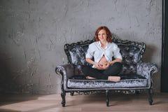 Schwangere Frau der Junge mit dem roten Haar, das auf einem grauen Sofa in der barocken Art sitzt Sie ` s, das ein weißes Hemd, s lizenzfreies stockfoto