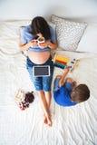 Schwangere Frau der Junge und ihr Kind, liegend im Bett mit Tablette Stockbilder