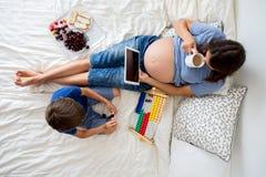 Schwangere Frau der Junge und ihr Kind, liegend im Bett mit Tablette Stockfotografie