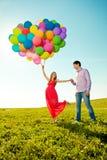 Schwangere Frau der jungen gesunden Schönheit mit ihrem Ehemann und Ballon Lizenzfreie Stockbilder