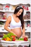 Schwangere Frau in der Küche, die einen Gemüsesalat zubereitet Gesundes nahrhaftes Stockbild