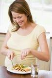 Schwangere Frau in der Küche Huhn essend Stockfoto
