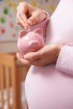 Schwangere Frau in der Kindertagesstätte, die Geld in Sparschwein steckt Lizenzfreie Stockfotografie