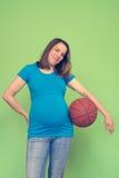 Schwangere Frau des Active, die einen Basketball hält Stockbild