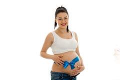 Schwangere Frau des Brunette mit bereits dem dicken Bauch, der im Studio auf dem weißen Hintergrund lokalisiert aufwirft Stockfotografie