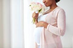 Schwangere Frau des glücklichen Afroamerikaners mit Blumen lizenzfreie stockfotografie
