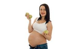 Schwangere Frau des glücklichen Brunette, die mit grünem Apfel in ihren Händen aufwirft und auf der Kamera lokalisiert auf weißem Stockfoto
