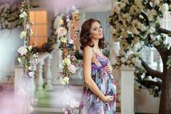 Schwangere Frau des schönen Brunette, die auf ein Baby in einem Purpur wartet Stockfotografie