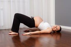 Schwangere Frau des smiley, die zu Hause Übung tut stockfotografie