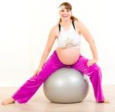 Schwangere Frau, die Übungen auf Eignungkugel tut Stockfotografie