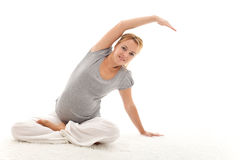 Schwangere Frau, die Übungen ausdehnend tut Stockbild