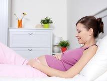 Schwangere Frau, die auf Bett liegt und ihren Bauch berührt Stockbild