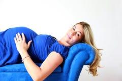 Schwangere Frau, die auf Couch stillsteht Lizenzfreie Stockfotos