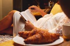 Schwangere Frau, die auf dem Bett am Schlafzimmer liegt und zu Hause ein Buch über Mutterschaft oder chicklit, den Roman der Frau stockfoto