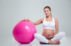 Schwangere Frau, die auf dem Boden mit Eignungsball sitzt Stockbilder