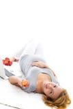 Schwangere Frau, die auf dem Fußboden sich entspannt Stockbilder