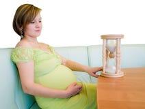 Schwangere Frau, die auf dem Hourglass schaut stockbild