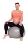 Schwangere Frau, die auf einem Ball sitzt stockfoto