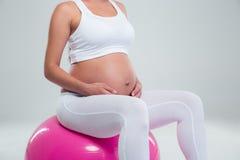 Schwangere Frau, die auf einem Eignungsball sitzt Lizenzfreie Stockbilder
