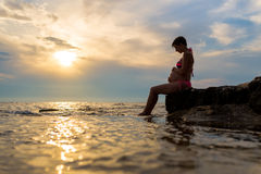 Schwangere Frau, die auf einem Felsen durch das Meer sitzt Lizenzfreie Stockbilder