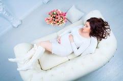 Schwangere Frau, die auf einem Sofa nahe einem Korb mit Tulpen liegt Stockbild