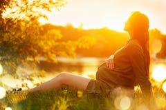 Schwangere Frau, die auf grünem Gras im Sommerpark, Natur genießend sitzt Gesunde Schwangerschaft stockfotos