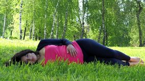 Schwangere Frau, die auf Gras liegt und ihren Magen streicht stock video