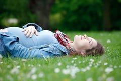 Schwangere Frau, die auf Gras sich entspannt lizenzfreie stockfotografie
