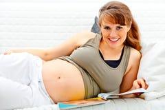 Schwangere Frau, die auf Sofa mit Zeitschrift sich entspannt Lizenzfreies Stockfoto