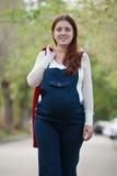 Schwangere Frau, die auf Straße geht Lizenzfreie Stockbilder